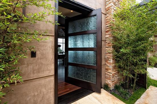 Внешнее формление входной деревянной двери со вставками из прочного стекла